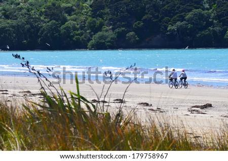 Senior couple riding bikes on the beach. - stock photo