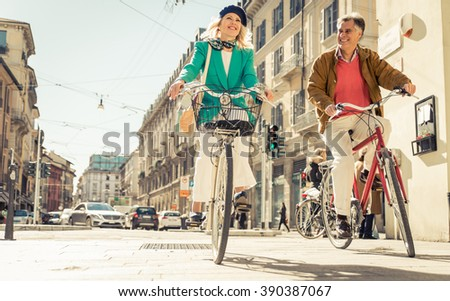 Senior couple riding their bicycle in the city center. Mature people making urban healthy lifestyle - stock photo