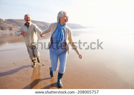 Senior Couple Running Along Winter Beach - stock photo