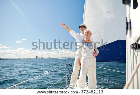 senior couple sailing on boat or yacht in sea - stock photo
