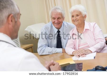Senior couple sat in doctors office - stock photo