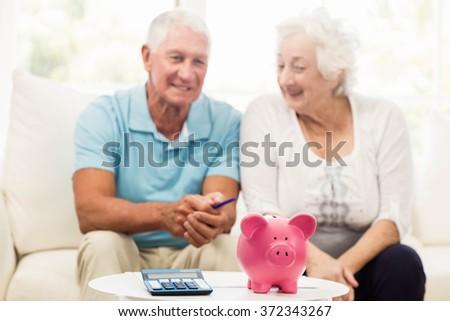 Senior couple saving money at home - stock photo