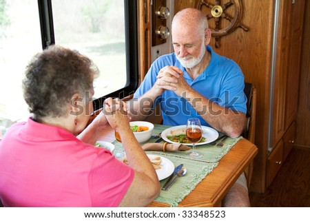 Senior couple say a prayer of thanksgiving over a turkey dinner in their motor home. - stock photo