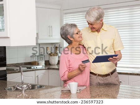 Senior couple shopping online with tablet pc at home in the kitchen - stock photo