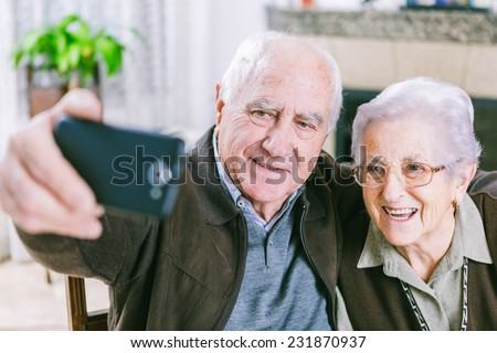 Senior couple showing self portrait photo on smartphone - stock photo