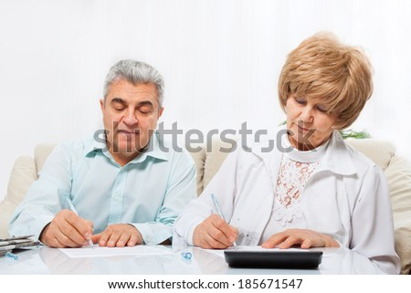 senior couple sign up document sitting at home sofa - stock photo