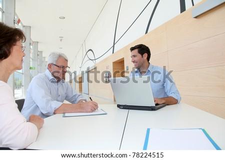 Senior couple signing contract - stock photo
