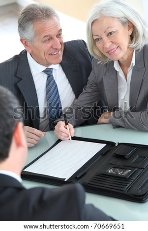 Senior couple signing home purchase contract - stock photo