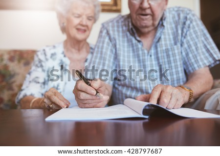 Senior couple signing will documents. Elderly caucasian man and woman sitting at home and signing some paperwork, focus on hands. - stock photo