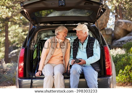 Senior couple sit in open car trunk before a hike, close-up - stock photo