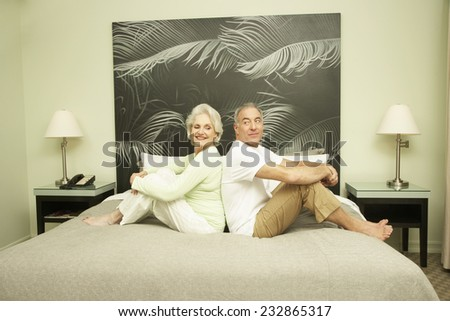 Senior Couple Sitting Back to Back on Bed in Hotel Room - stock photo