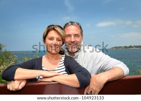 Senior couple sitting in front of beautiful sea view - stock photo