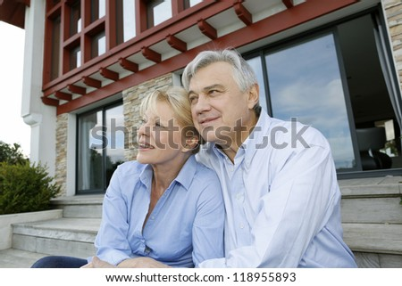 Senior couple sitting in front of house and looking away - stock photo