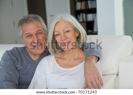 Senior couple sitting in sofa at home - stock photo