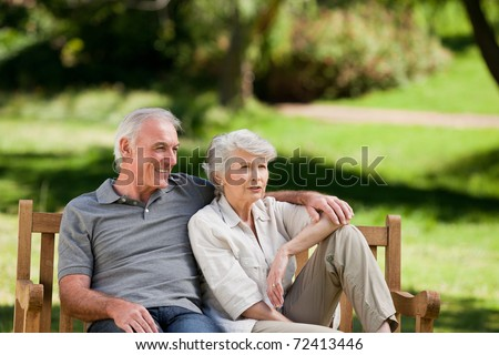 Senior couple sitting on a bench - stock photo