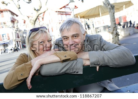 Senior couple sitting on a public bench - stock photo
