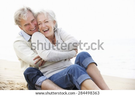 Senior Couple Sitting On Beach Together - stock photo