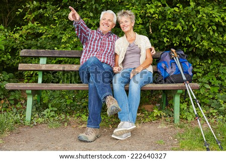 Senior couple sitting on bench during hiking trip in nature - stock photo