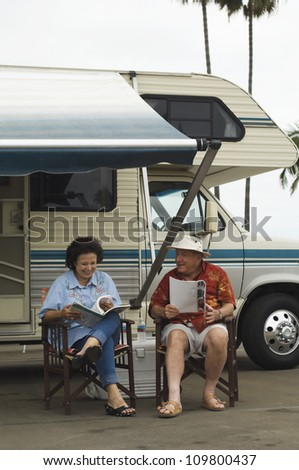 Senior couple sitting on chair with caravan in the background - stock photo
