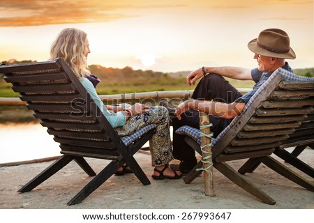 Senior couple sitting on chairs with their backs at the camera on sunset time in Chitwan national park, Nepal - stock photo