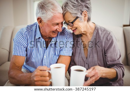 Senior couple sitting on sofa and having coffee in living room - stock photo