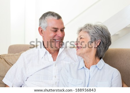 Senior couple sitting on sofa smiling at each other at home in living room - stock photo