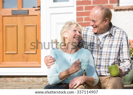Senior Couple Sitting Outside Hose With Cup Of Coffee - stock photo