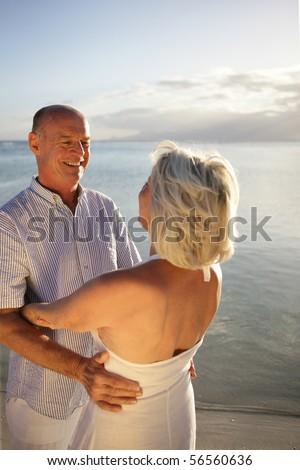 Senior couple smiling embracing next to the sea - stock photo