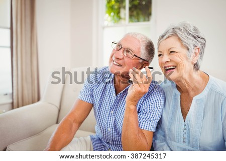 Senior couple smiling while talking on mobile phone - stock photo