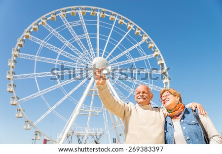 Senior couple taking a selfie at amusement park with panoramic wheel - Two persons in the 60's having fun with new technologies outdoor - Husband taking a photograph with his wife on vacation - stock photo