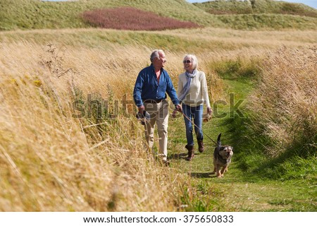 Senior Couple Taking Dog For Walk In Countryside - stock photo
