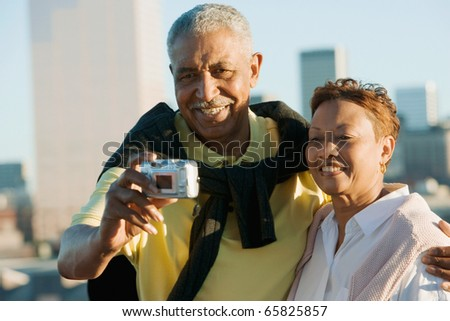 Senior couple taking pictures of themselves with city behind them - stock photo