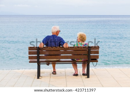 Senior couple talking at the beach in a cloudy day at the shores of the Ionian see in Kefalonia island, Greece. - stock photo