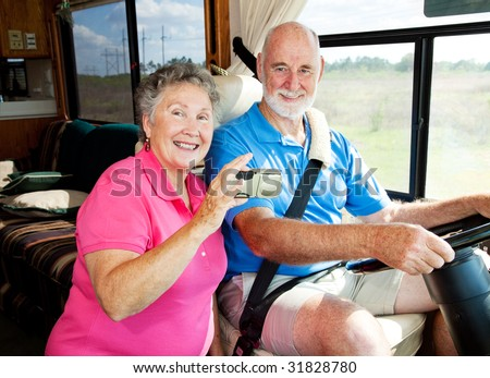 Senior couple using a GPS to navigate their motor home on the road. - stock photo