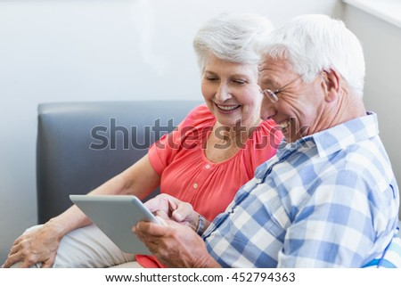 Senior couple using a tablet in a retirement home - stock photo