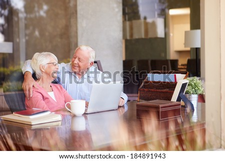 Senior Couple Using Laptop On Desk At Home - stock photo