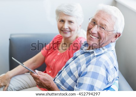 Senior couple using tablet in a retirement home - stock photo