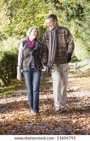 Senior couple walking along autumn path through woods - stock photo