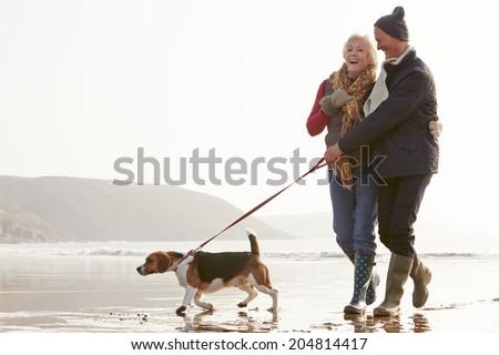 Senior Couple Walking Along Winter Beach With Pet Dog - stock photo