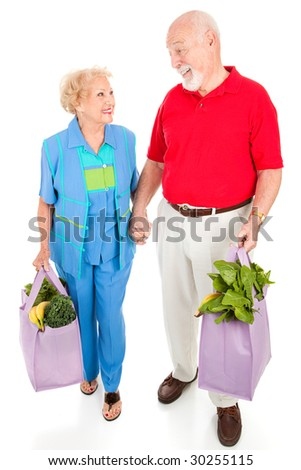Senior couple walking home with their groceries in reusable shopping bags.  Isolated on white. - stock photo