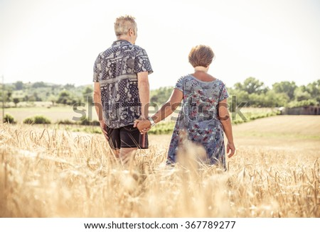 Senior couple walking in the countryside and having fun. People and seniority - stock photo