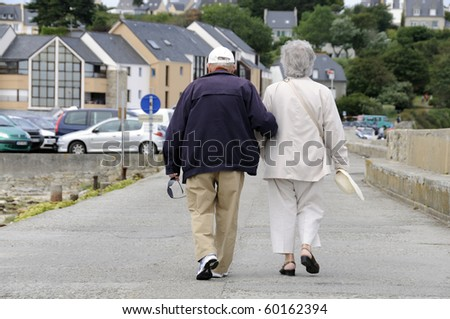 Senior couple walking together holding their hands. - stock photo