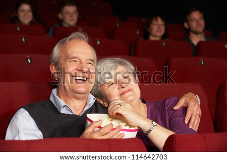 Senior Couple Watching Film In Cinema - stock photo