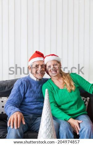 senior couple wear red santa christmas hat present, sitting on sofa smile - stock photo
