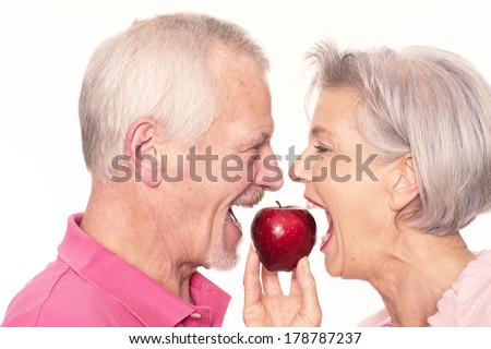 Senior couple with apple in front of white background - stock photo