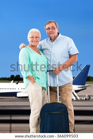 Senior couple with bags at airport - stock photo