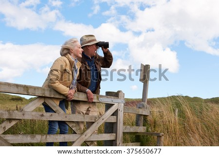 Senior Couple With Binoculars Walking In Countryside - stock photo