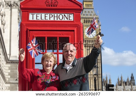 Senior couple with red telephone box holding British flag in London. Big Ben in the background. - stock photo
