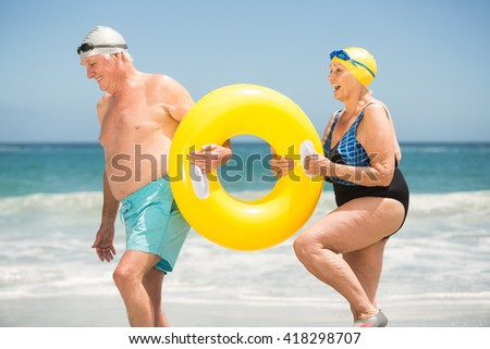 Senior couple with swimming ring at the beach on a sunny day - stock photo