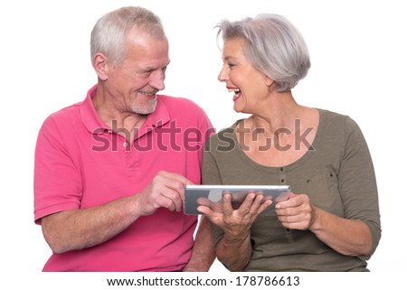 Senior couple with tablet computer in front of white background - stock photo